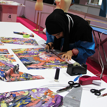Hessa Al Shawab working on her blouse